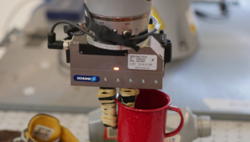 Close-up-shot-of-DON-system-and-Kuka-Robot-grasping-a-cup