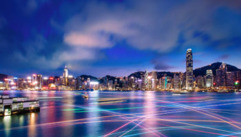 The world famous night scene of Hong Kong city skyline with busy water traffic navigate across Victoria Harbour